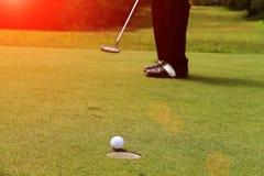 Golfare sätter golf i aftongolfbanan Arkivfoto