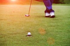 Golfare sätter golf i aftongolfbanan i Thailand Arkivfoto