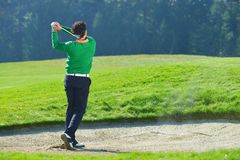 Golfare som gå i flisor bollen från sandfälla Royaltyfri Fotografi