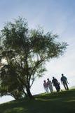 Golfare som går på golfbana Arkivfoto
