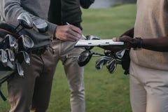 Golfare som rymmer klubbor i påsar och undertecknar legitimationshandlingar på skrivplattan Royaltyfri Fotografi