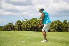 Golfare som slår bollen på härlig golfbana royaltyfri bild