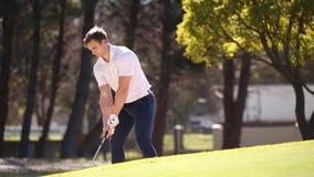 Golfare som slår en chip stock video
