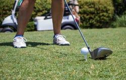 Golfare som slår golfboll av utslagsplats arkivfoto