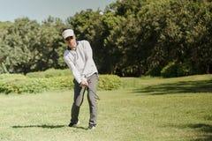 Golfare som slår golfboll på grönt gräs för farled royaltyfri fotografi
