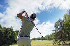 Golfare som sl?r golfskottet med klubban p? kurs medan p? sommarsemester royaltyfri foto