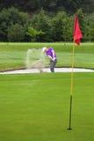Golfare som spelar ut ur en bunker Arkivbilder