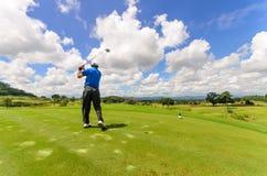 Golfare som svänger hans kugghjul och slår golfbollen Arkivbild