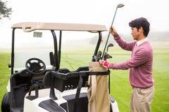 Golfare som tar klubban i golfpåse Arkivfoto