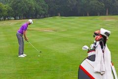 Golfare som tilltalar bollen på en farled för medeltal 4. Royaltyfria Bilder