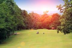 Golfare spelar golf i aftongolfbanan Royaltyfri Bild