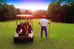 Golfare spelar golf och golfvagnen i aftongolfcoursna Arkivbild