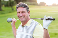 Golfareanseende och svänga hans klubba som ler på kameran Arkivfoto