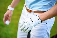 Golfareinnehavboll och golfklubb arkivbild