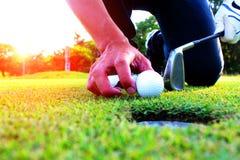 Golfathleten setzen sich hin, um Golfball im grünen Rasen zu fangen lizenzfreie stockbilder