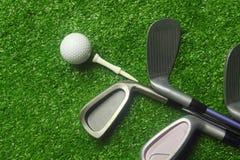 Golfb?lle und Golfclubs auf gr?nem Gras lizenzfreie stockfotografie