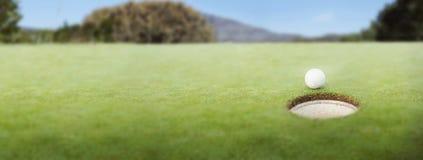 Golfbal bij de rand van het gat royalty-vrije stock foto