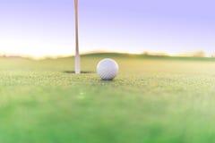 Golfbal dicht bij gat op groen Stock Foto