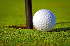 Golfbal dichtbij het gat Royalty-vrije Stock Afbeeldingen