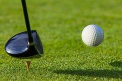 Golfbal die van het T-stuk met bestuurder op golf wordt geraakt cour Royalty-vrije Stock Afbeeldingen