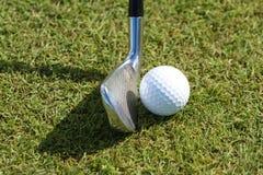 Golfbal en club in gras Stock Foto