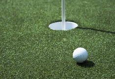 Golfbal en gat op een gebied Royalty-vrije Stock Afbeeldingen