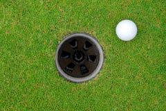 Golfbal en golfgat op groen gras stock fotografie