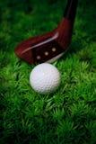 Golfbal en houten bestuurder op groen gras van golf c Stock Foto