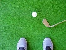 Golfbal en ijzergolfclub met golfspeler royalty-vrije stock foto's