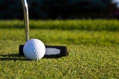 Golfbal en putter op green stock foto