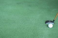 Golfbal en putter op groen gras royalty-vrije stock fotografie