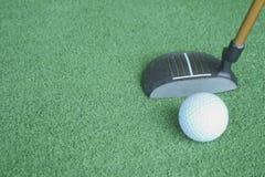Golfbal en putter op groen gras royalty-vrije stock foto