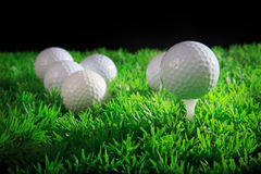 Golfbal en T-stuk in groen gras Royalty-vrije Stock Afbeeldingen