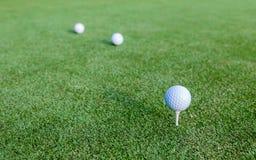 Golfbal en T-stuk op groen gras tijdens opleiding Stock Afbeelding