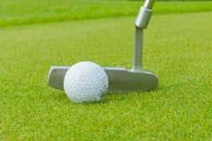 Golfbal en T-stuk op groene cours Stock Foto