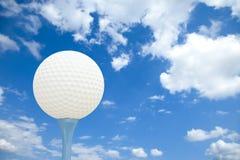 Golfbal en T-stuk voor een bewolkte hemel Stock Afbeeldingen