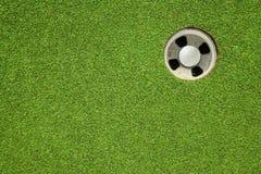 Golfbal in het gat Stock Afbeeldingen
