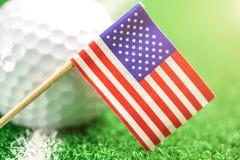 Golfbal met de vlag van de V.S. op groen gazon of gebied Royalty-vrije Stock Afbeelding