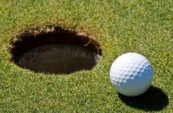 Golfbal naast een gat Royalty-vrije Stock Afbeelding