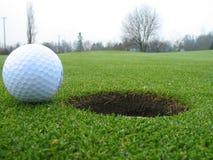 Golfbal naast gat Stock Fotografie