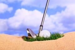 Golfbal op een bosje van gras in bunker Stock Afbeeldingen