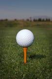 Golfbal op een oranje T-stuk stock foto