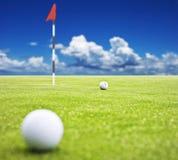 Golfbal op groen zetten Stock Afbeeldingen