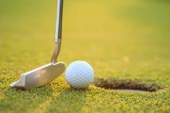 Golfbal op lip van kop in cursus stock fotografie