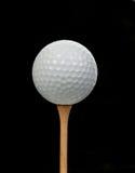 Golfbal op T-stuk op zwarte Stock Afbeeldingen