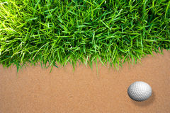Golfbal op zand Stock Foto's