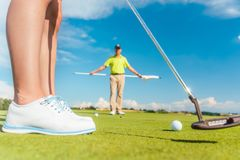 Golfbal op zetten groen achter de lage sectie van een vrouwelijke speler royalty-vrije stock afbeelding