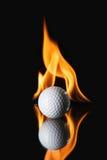 Golfbal op zwarte achtergrond met brand stock afbeelding