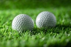 Golfbal twee op gras stock afbeelding
