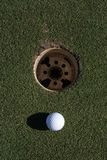 Golfball. Golf ball lying close to the hole Royalty Free Stock Photography
